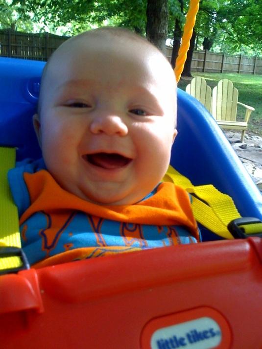 leo smiling in swing